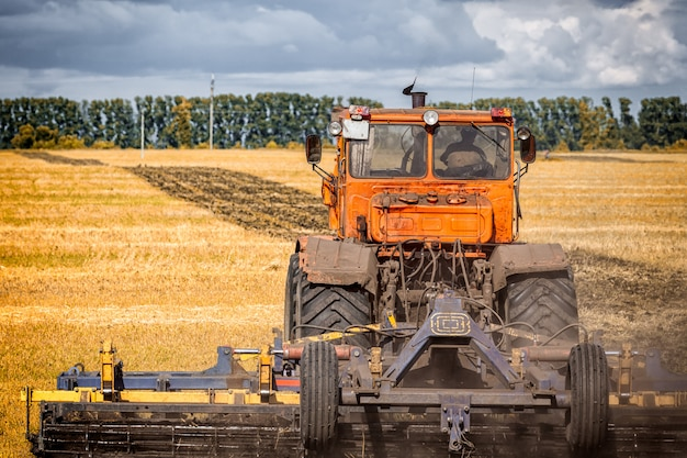 An orange modern tractor plows the earth inâ a golden field of wheat on a summer day Premium Photo