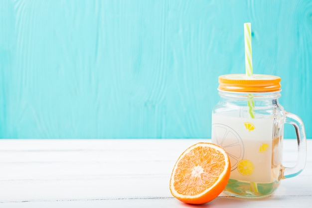 Orange near glass with straw and lemonade Free Photo