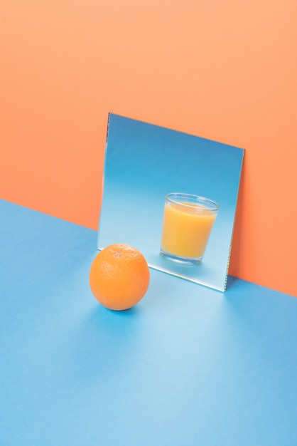 Orange near juice in mirror on blue table isolated Free Photo