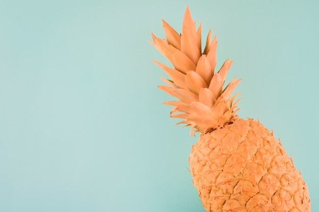 An orange painted pineapple on the corner of blue background Free Photo