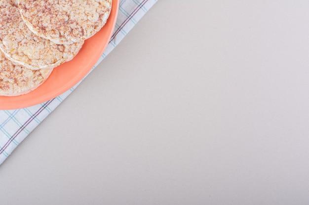 흰색 테이블에 맛있는 떡의 오렌지 플레이트. 고품질 사진 무료 사진