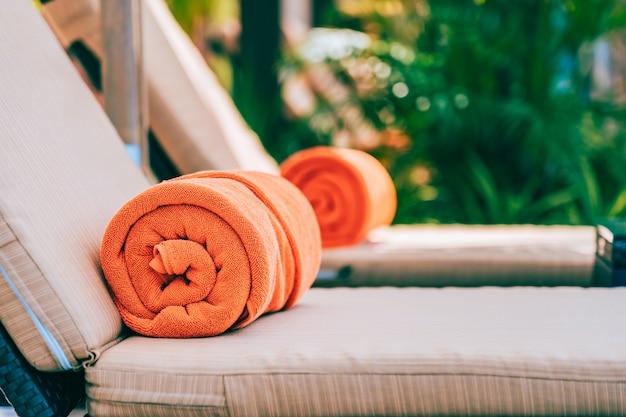 Orange pool towel on deck chair Free Photo