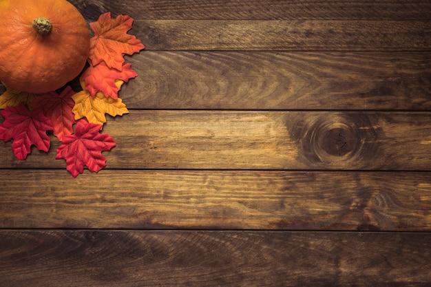 Orange pumpkin lying with autumn leaves Free Photo