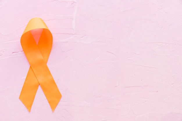 Orange ribbon for raising awareness on leukemia, kidney cancer rds multiple sclerosis, and adhd illness on pink background Premium Photo