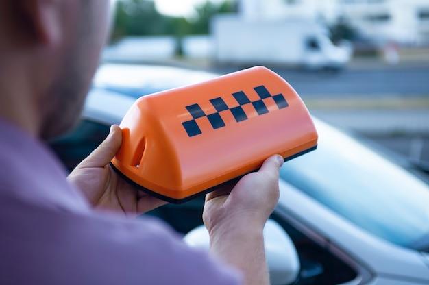 Оранжевый знак такси в руках мужчины на фоне автомобиля. Premium Фотографии