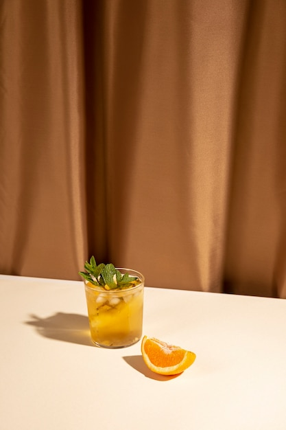 Orange slice and cocktail drink glass on white table near brown curtain Free Photo