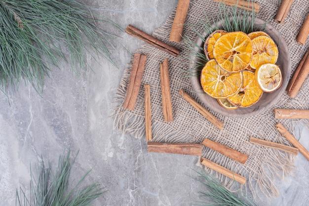 Дольки апельсина в деревянной чашке с палочками корицы вокруг Бесплатные Фотографии