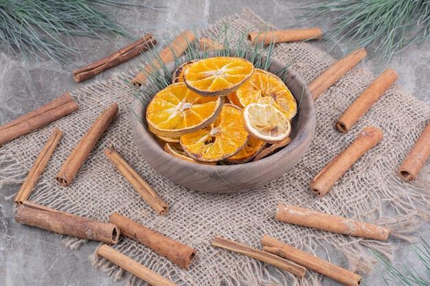 シナモンスティックが付いている木製のカップのオレンジスライス 無料写真