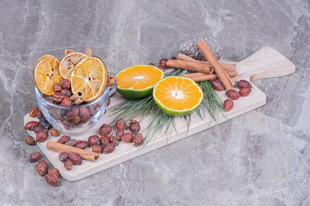 木製の大皿にドライヒップとシナモンスティックのオレンジスライス 無料写真