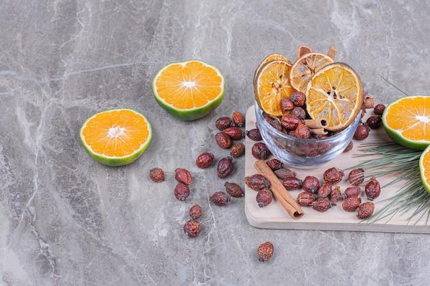 마른 엉덩이와 계피 스틱이 나무 접시에 담긴 오렌지 슬라이스 무료 사진