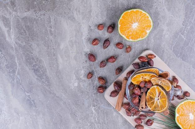 木製の大皿に腰とシナモンのオレンジスライス 無料写真