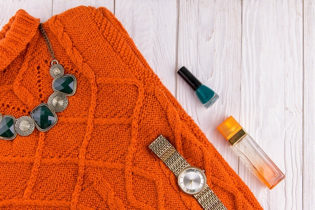 Orange sweater with accessories and cosmetics. female outfit on wooden background Premium Photo