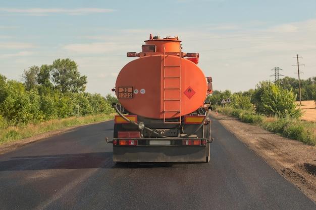 オレンジ色のタンクローリーは青い空を背景に田舎道に乗る。背面図 Premium写真