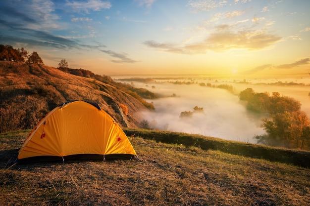 Оранжевый шатер в каньоне над туманной рекой на закате Premium Фотографии