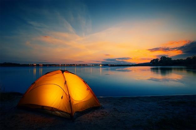 Оранжевая палатка на озере в сумерках Premium Фотографии