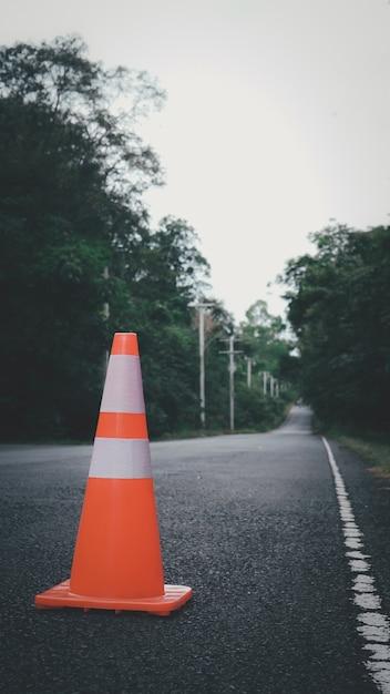 オレンジ色のトラフィックコーンタイの田舎道で車に乗り込まないように警告するために使用されます。 Premium写真