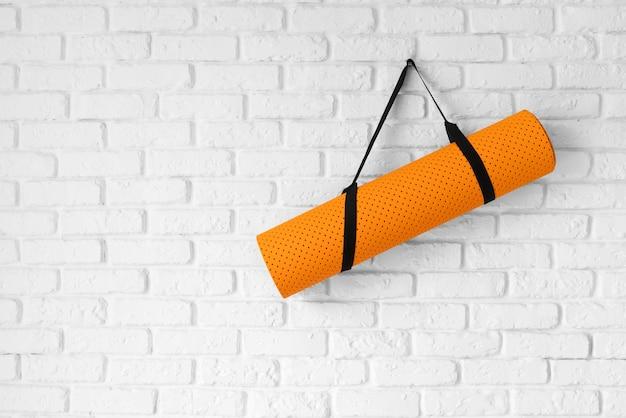 Оранжевый коврик для йоги, висящий на стене Premium Фотографии