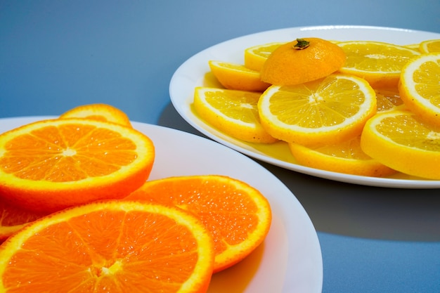 Апельсины и желтые лимоны на тарелке в солнечный день Бесплатные Фотографии