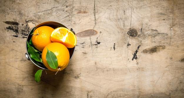 葉のバケツの中のオレンジ。木製の背景に。 Premium写真