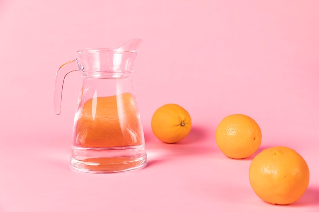 Oranges and jug of water on pink background Free Photo