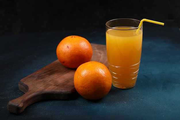 Oranges on a wooden board with a glass of juice. black background. Free Photo