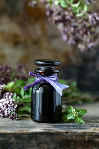 木製の背景にガラス瓶の中のオレガノのエッセンシャルオイル。コピースペース 無料写真
