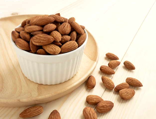 Organic almonds in ceramic bowl with wooden tray and heap almonds on wooden Premium Photo