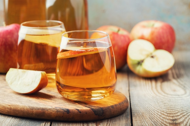 Organic apple cider or juice on a wooden table. two glasses with drink and autumn leaves on rustic background. Premium Photo
