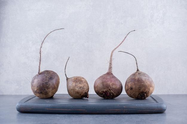 Органические свеклы на деревянном блюде, изолированные на сером фоне бетона. Бесплатные Фотографии