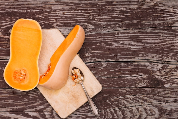 An organic butternut squash and seeds on spoon over the chopping board against the wooden desk Free Photo