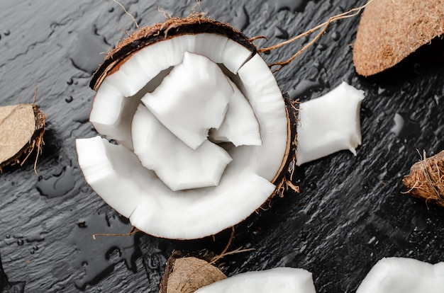 Organic coconut hlf with pieces on black slate stone background. healthy high fat foods concept. Premium Photo