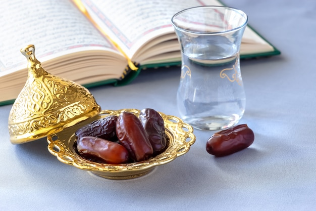 Organic dried dates, cup of pure drinking water and quran book Premium Photo