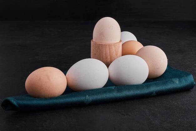 緑のテーブルクロスに有機卵。 無料写真