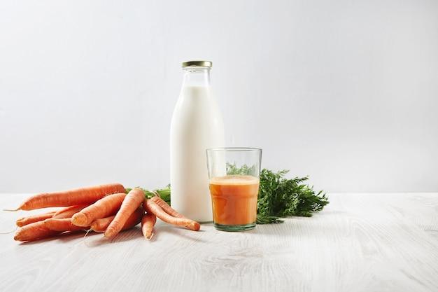 Raccolta della carota dell'azienda agricola biologica che si trova vicino alla bottiglia con latte e bicchiere riempito a metà con succo fresco naturale per la colazione. Foto Gratuite