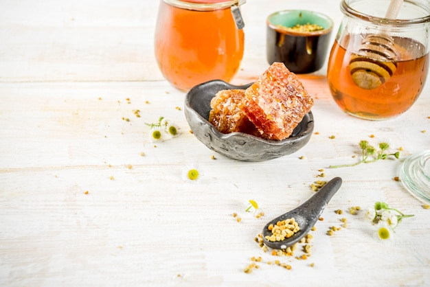 Organic floral honey, in jars, with pollen and honey combs, on a white wooden table, with wildflowers Premium Photo