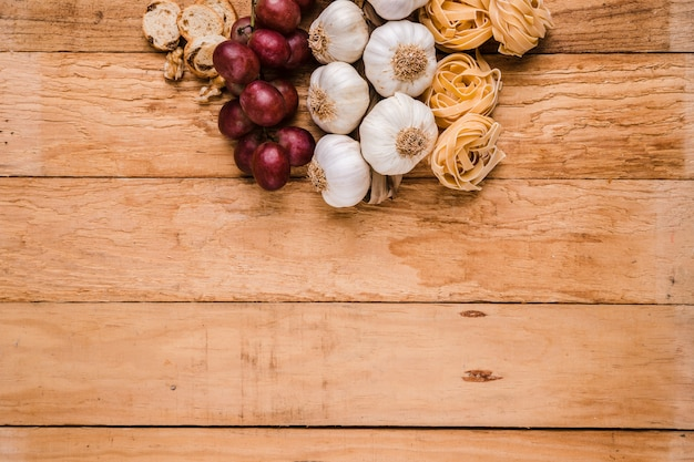 Organic grapes; bunch of garlic bulbs with raw pasta and bread over textured wallpaper Free Photo