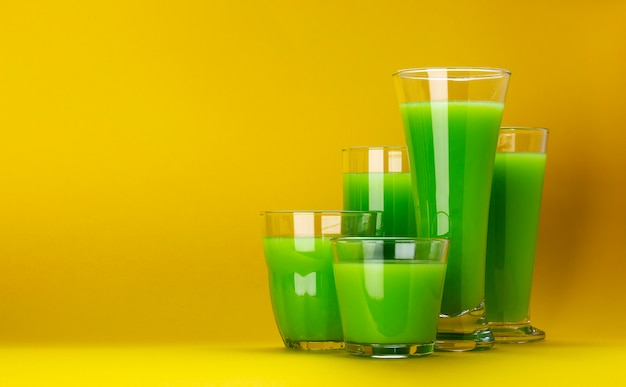 Organic green smoothie glasses isolated on yellow background Premium Photo