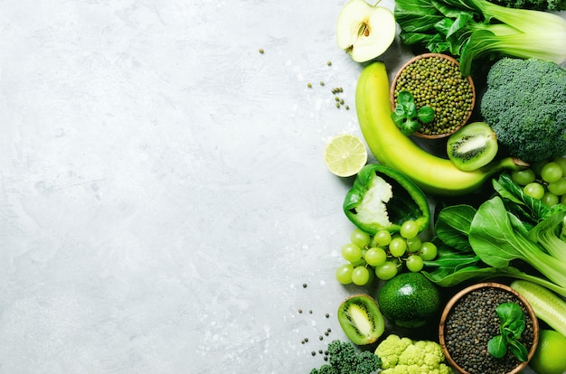 Organic green vegetables and fruits on grey. copy space, flat lay, top view. green apple, zucchini, cucumber, avocado, kale, lime, kiwi, grapes, banana, broccoli, marbled lentils, mung bean Premium Photo