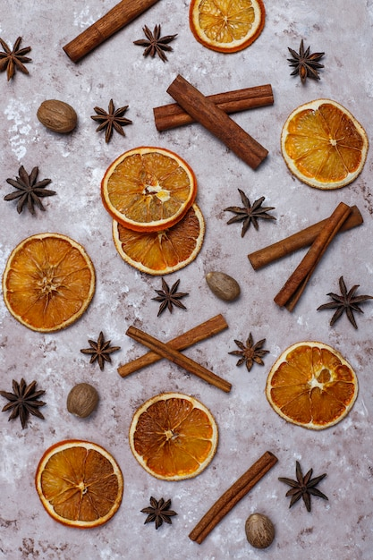 Organic homemade dried orange chips slices,nuts,star anise,cinnamon sticks on light brown surface Free Photo