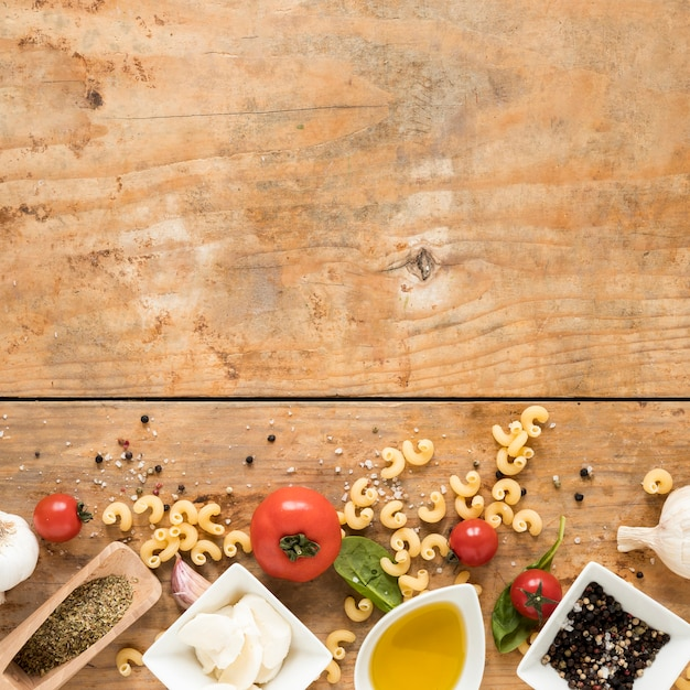 Organic italian ingredients and raw macaroni pasta over wooden table with space for text Free Photo