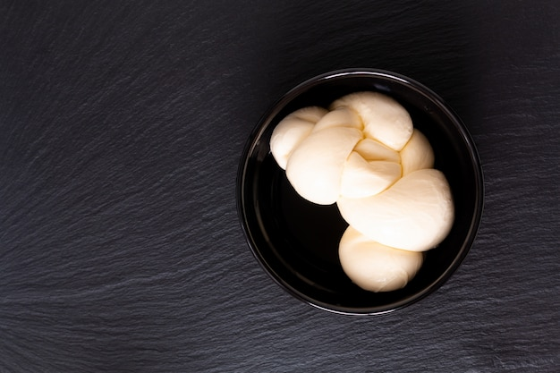 Organic mozzarella cheese in black ceramic cup with copy space Premium Photo
