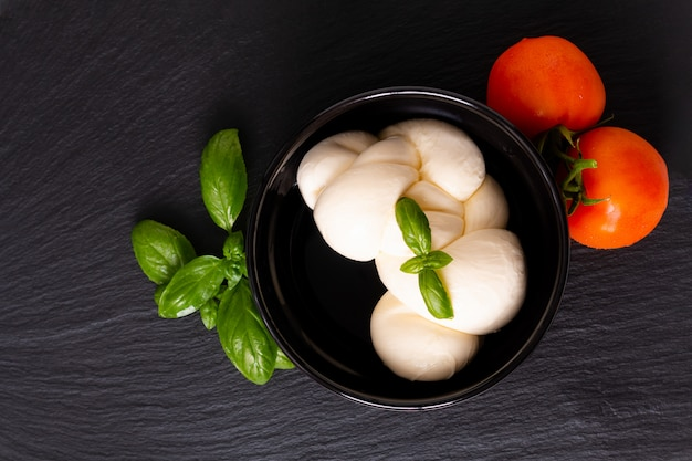 Organic mozzarella cheese in black ceramic cup with  tomatoes and basil with copy space Premium Photo