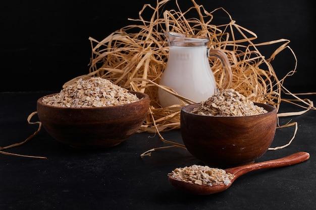牛乳の瓶と木製のカップとスプーンで有機ミューズリー。 無料写真