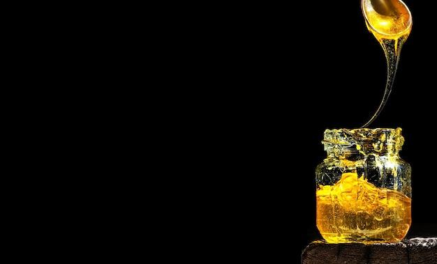 Miele naturale biologico, illuminato dalla luce solare, in un barattolo di vetro Foto Gratuite