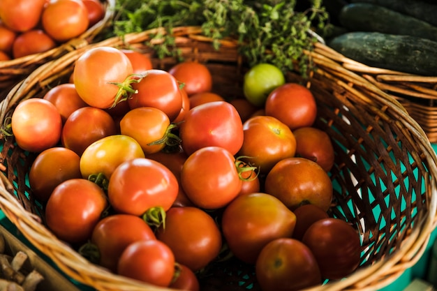 Organic red tomato wicker basket at grocery store market Free Photo
