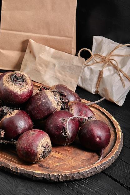 Органическая селективная свекла на деревянной доске на темном фоне. Premium Фотографии