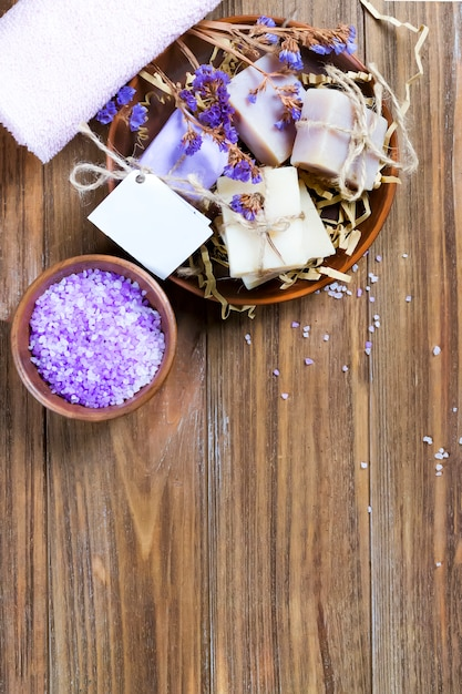 Organic soap in a basket with dry flowers and natural sea salt in a bowl on a brown wooden table with copy space. Premium Photo