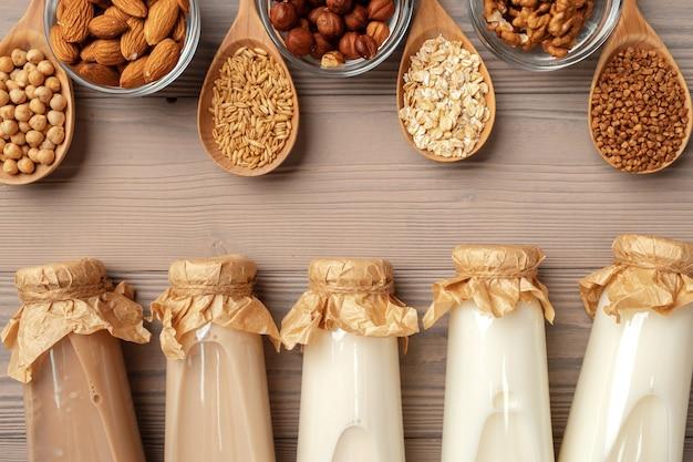 ガラスの牛乳瓶と木製の背景にバルク製品と有機ビーガン非乳製品牛乳 Premium写真