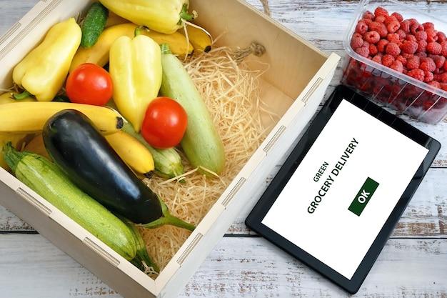 木製の箱やタブレットpcの有機野菜や果物 Premium写真
