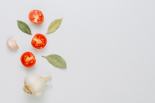 An organic whole garlic bulb and clove with bay leaves and halved cherry tomatoes on white backdrop Free Photo